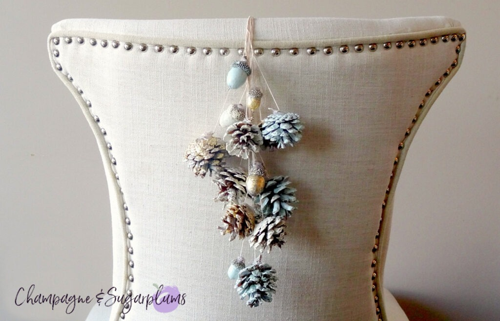 Painted pine cones and acorns hanging from the back of a chair by Champagne and Sugarplums