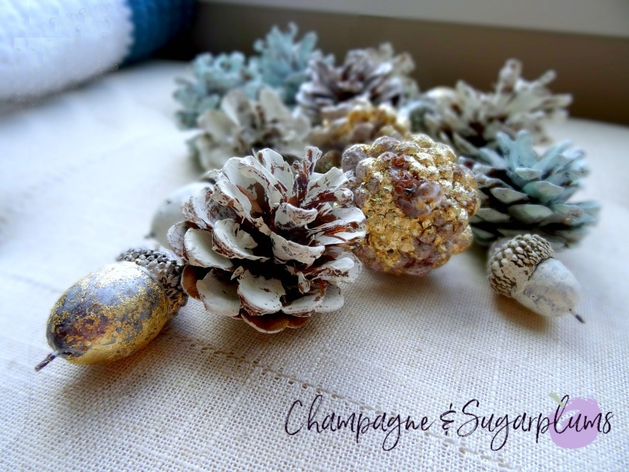 Painted pine cones and acorns on a bench by Champagne and Sugarplums