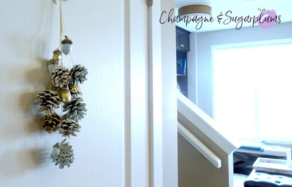 Painted pine cones and acorns hanging on a door by Champagne and Sugarplums