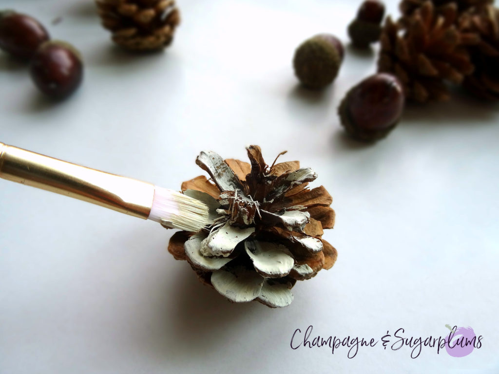 Pinecone being painted cream by Champagne and Sugarplums