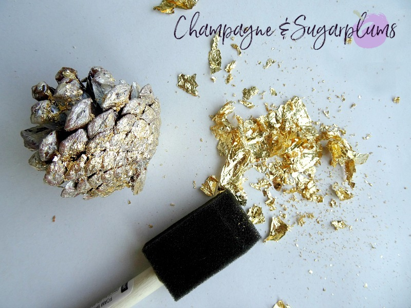 Gold gilding being added to a pinecone by Champagne and Sugarplums