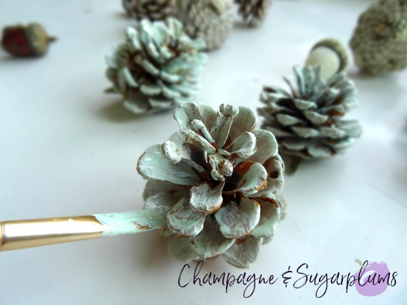 Pinecone being painted blue by Champagne and Sugarplums