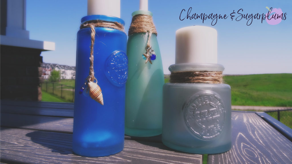 Sea glass bottles on a table outside on a sunny day by Champagne and Sugarplums