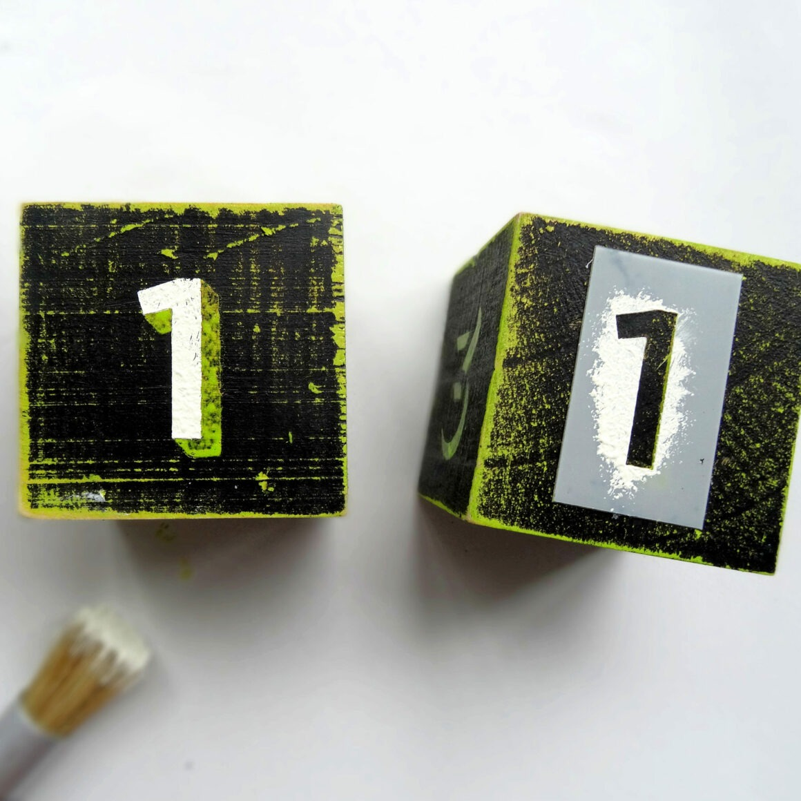 Two wooden blacks painted in black and green with the number one on them by Champagne and Sugarplums