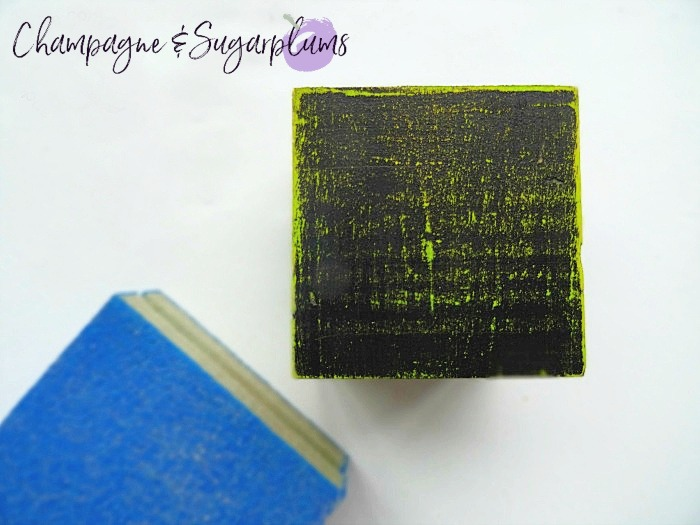 Distressing a wood block with sandpaper by Champagne and Sugarplums