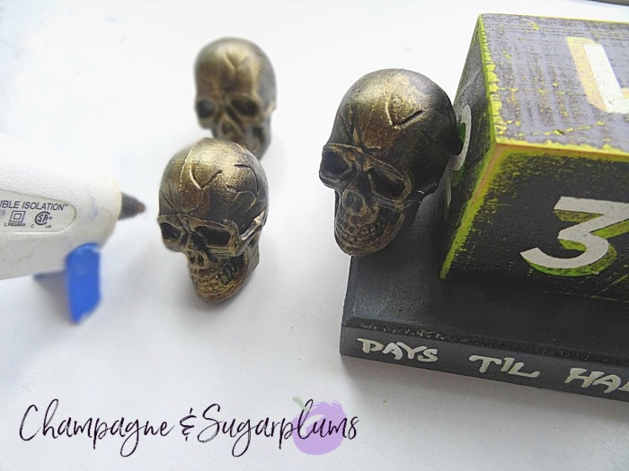 Gluing mini plastic skulls onto a wood block by Champagne and Sugarplums