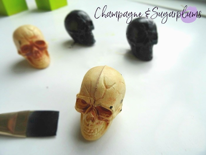 Small plastic skulls being painted black by Champagne and Sugarplums