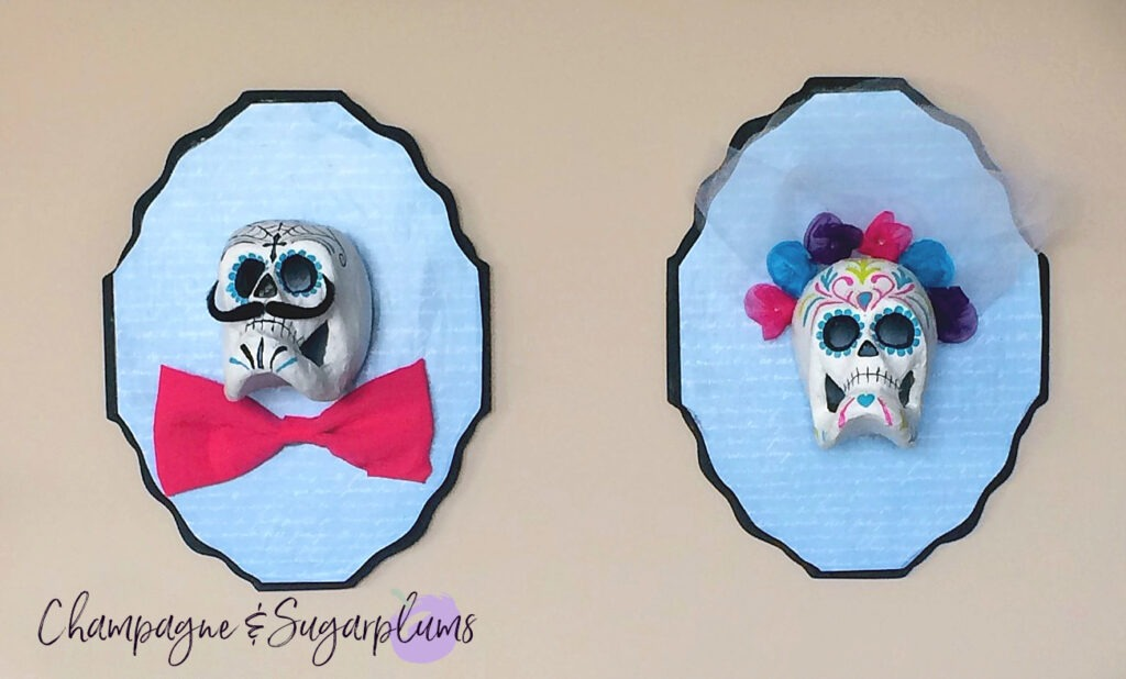 Sugar skulls hanging on a wall by Champagne and Sugarplums