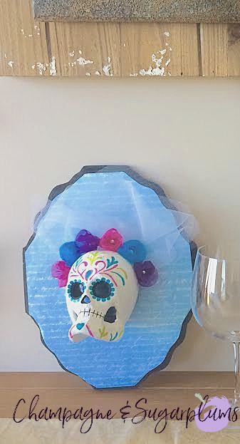 Sugar skulls on a table with wine bottles and glasses by Champagne and Sugarplums