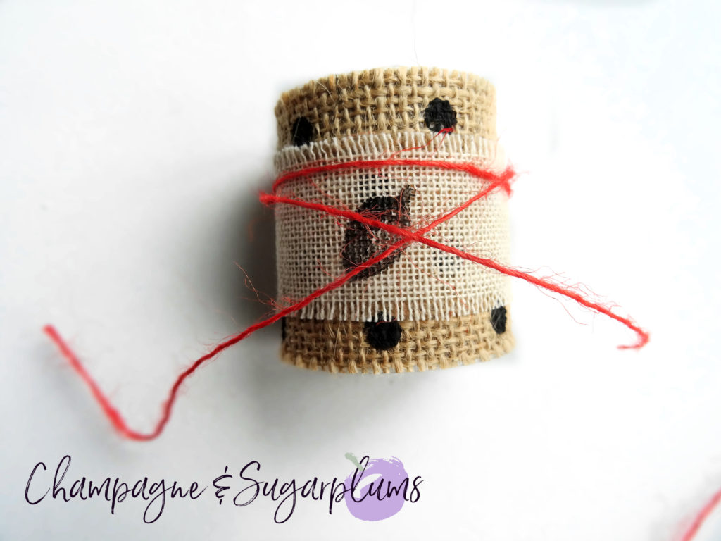 Adding orange twine to Thanksgiving napkin rings by Champagne and Sugarplums