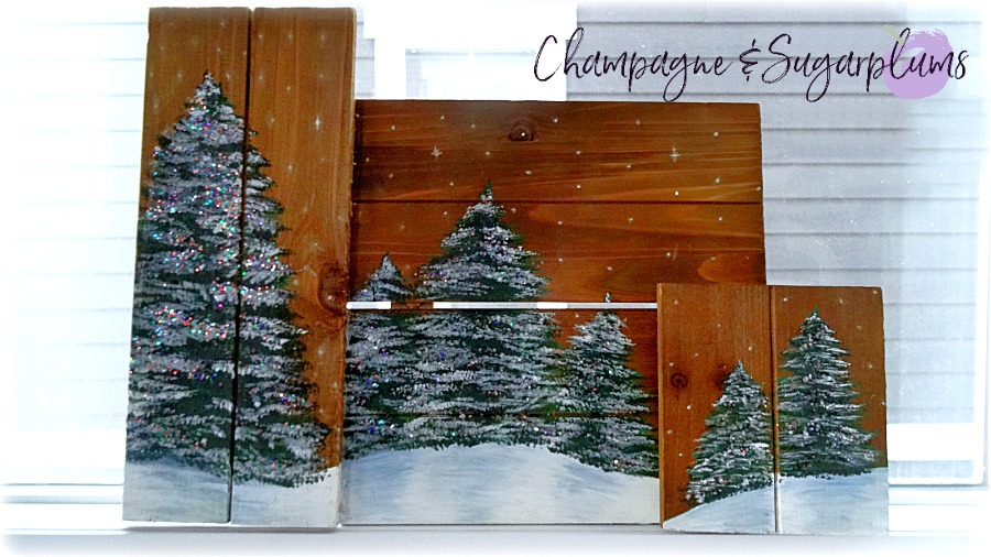 Painted holiday trees with glitter twinkle lights on wood planks in a window by Champagne and Sugarplums