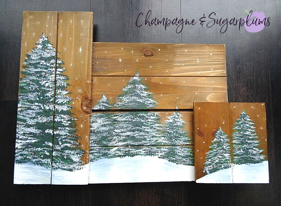Painted holiday trees with glitter twinkle lights on wood planks on a dark background by Champagne and Sugarplums