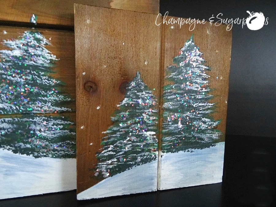 Painted holiday trees with glitter twinkle lights on wood planks by Champagne and Sugarplums