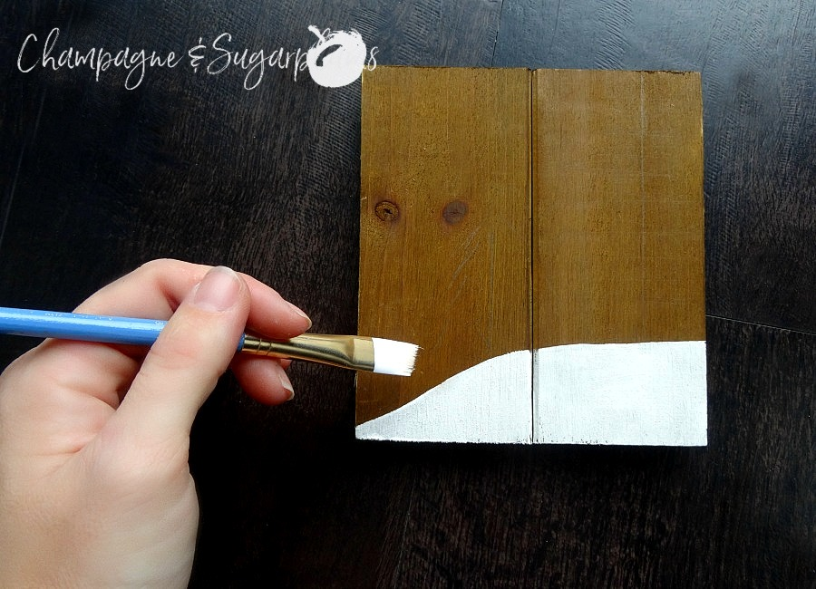 Painting a snow bank onto a wood plank by Champagne and Sugarplums