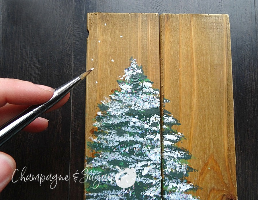 Painting snowflakes onto a wood planks around trees by Champagne and Sugarplums