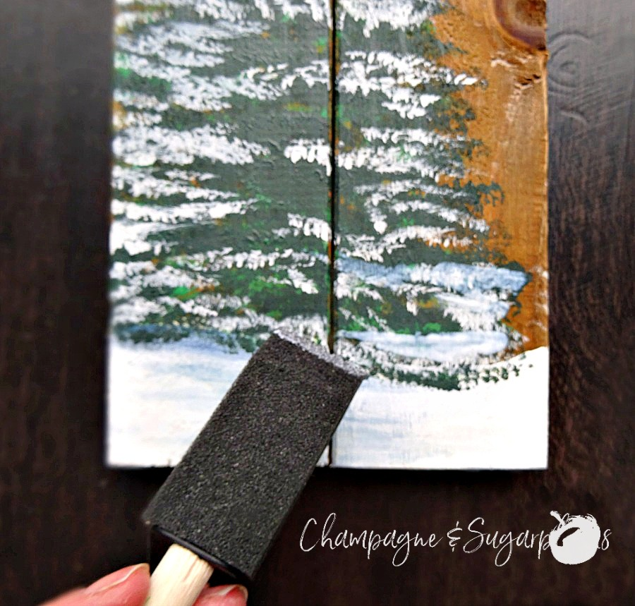 Adding glitter twinkle lights to trees by Champagne and Sugarplums