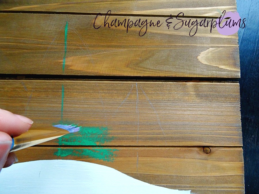 Painting green branches onto wood planks by Champagne and Sugarplums