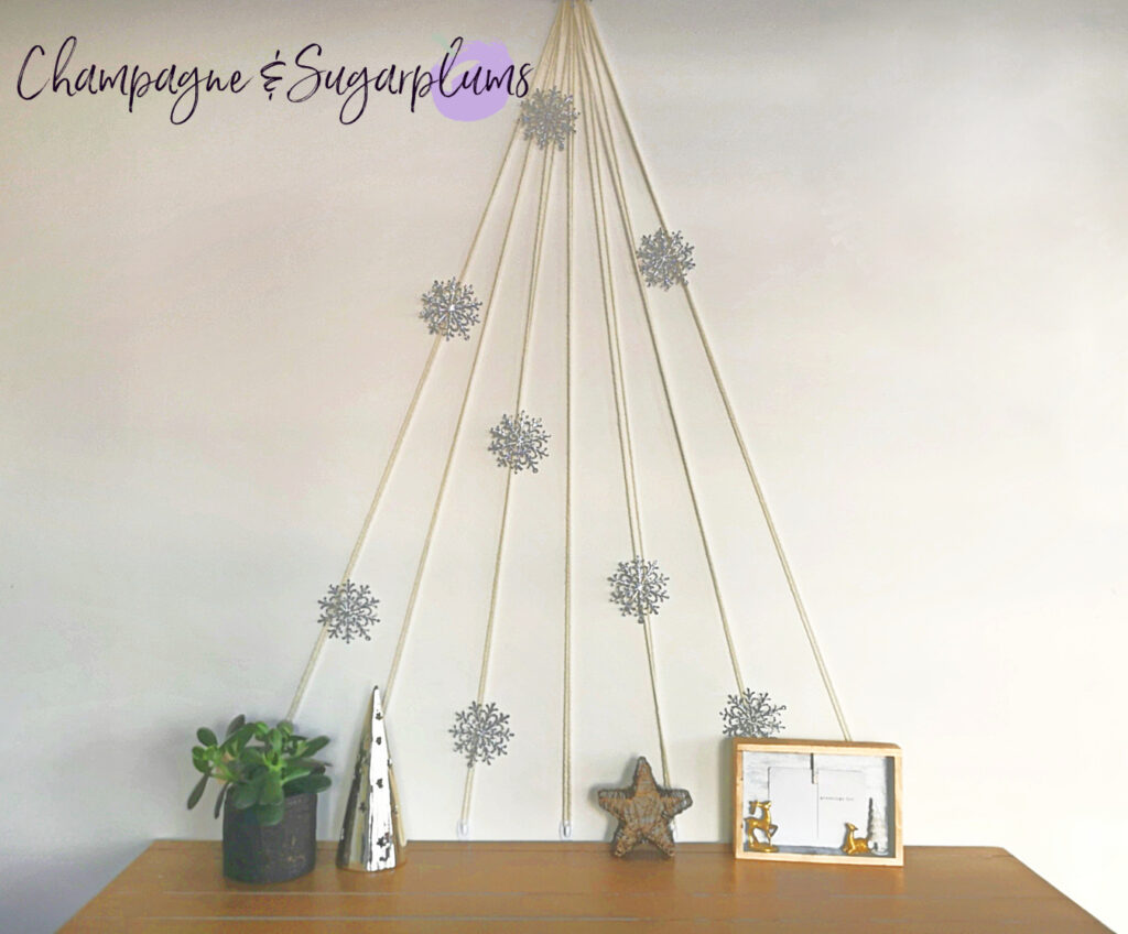 Modern Christmas tree made of yarn on a white wall above a table by Champagne and Sugarplums
