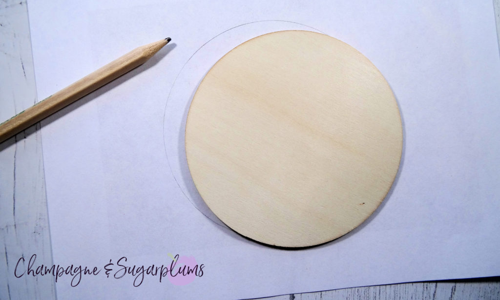 Tracing the shape of a wood coaster onto white paper by Champagne and Sugarplums