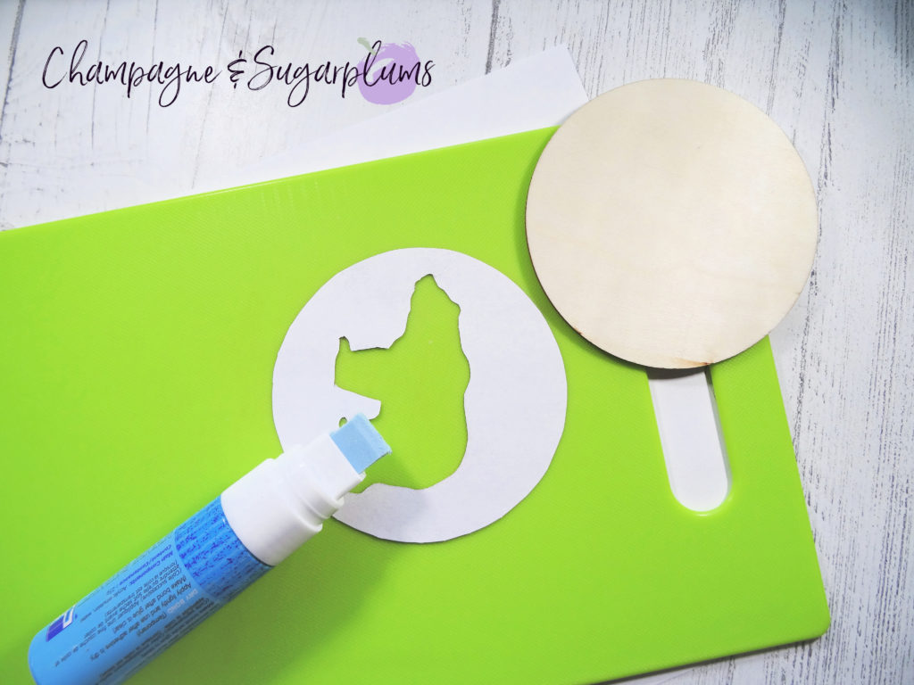 Adding glue to a paper shape by Champagne and Sugarplums