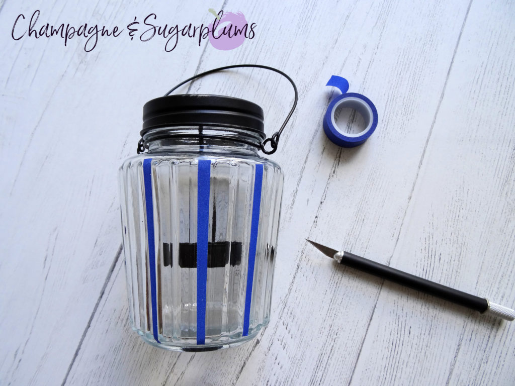 Adding blue tape to a glass candle jar by Champagne and Sugarplums