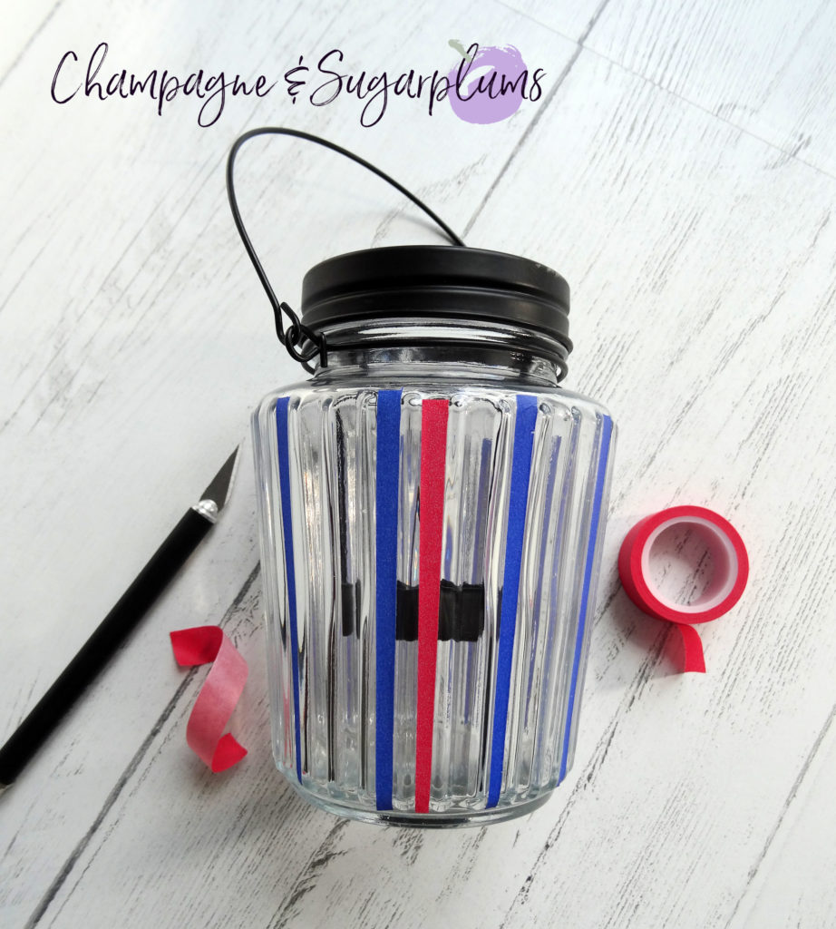 Adding red tape to a glass candle jar by Champagne and Sugarplums