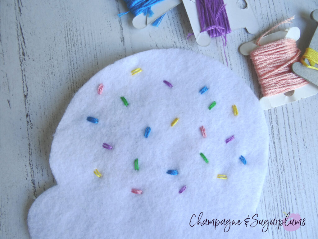 Sewing coloured threads onto white felt by Champagne and Sugarplums