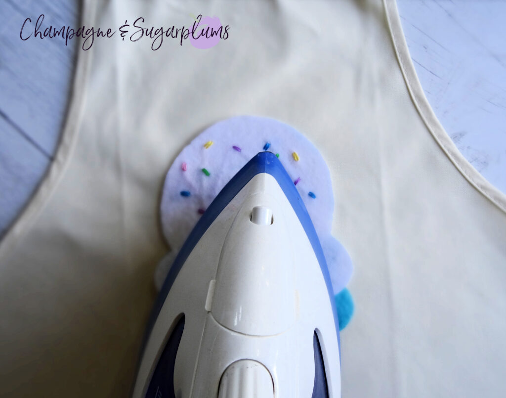 Ironing felt ice cream shapes onto white apron by Champagne and Sugarplums