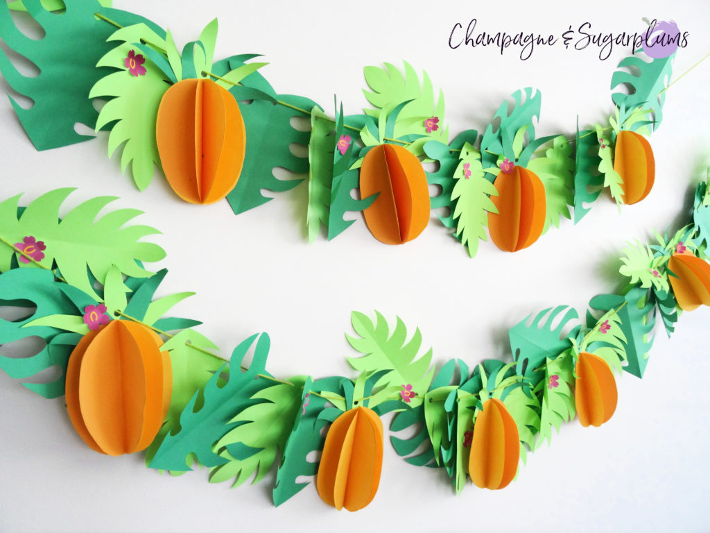 Tropical party decor garland on a white wall by Champagne and Sugarplums