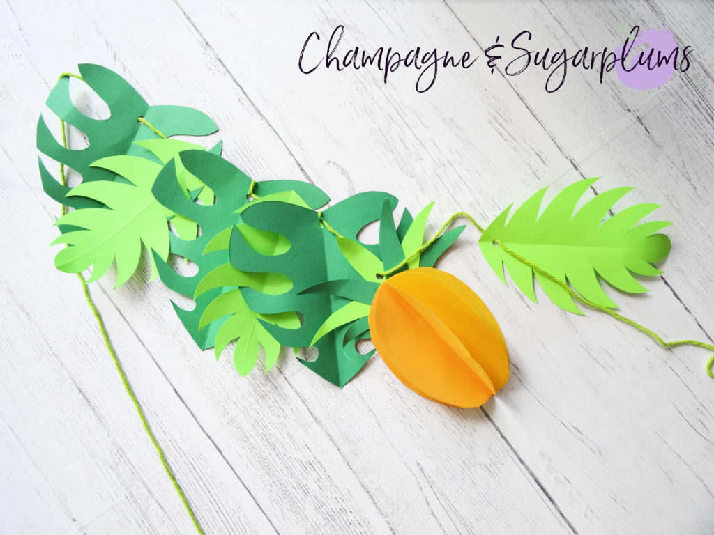 Stringing paper leaves and pineapples onto yarn by Champagne and Sugarplums