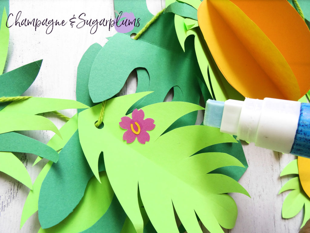 Gluing pink flowers onto green paper leaves by Champagne and Sugarplums