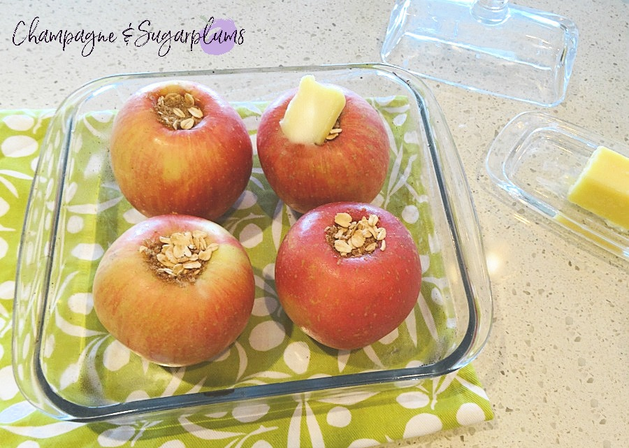 Baked Apples in a baking dish, covered in butter, by Champagne and Sugarplums