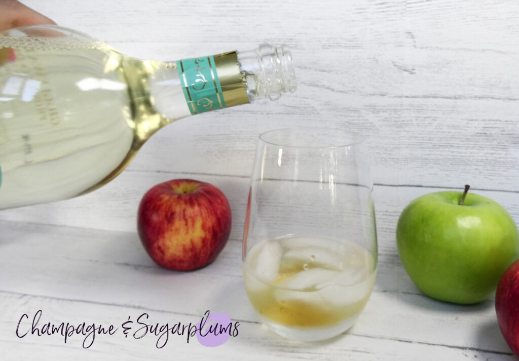 Pouring Prosecco into a cocktail glass with ice in it by Champagne and Sugarplums