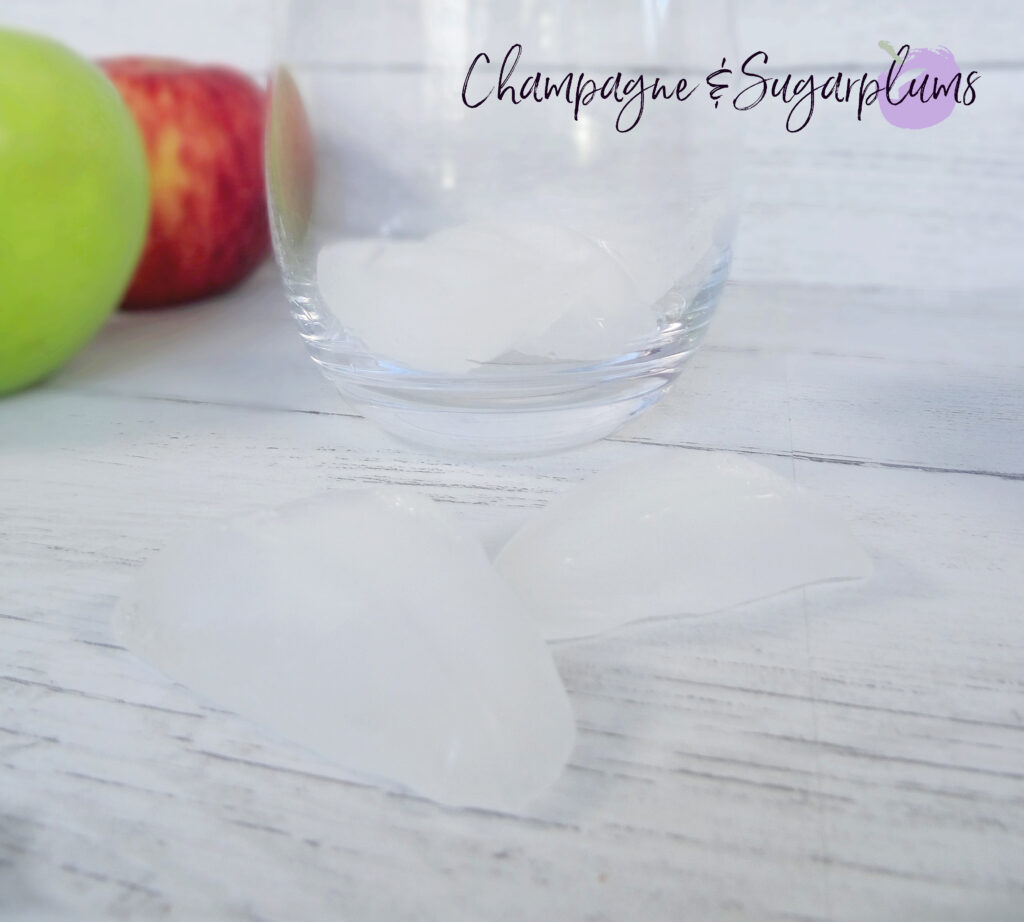 Adding ice cubes to a cocktail glass by Champagne and Sugarplums