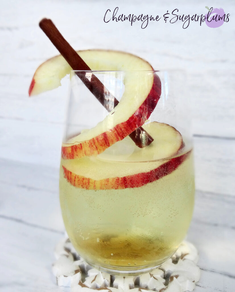 Adding an apple ring and a cinnamon stick to a cocktail by Champagne and Sugarplums