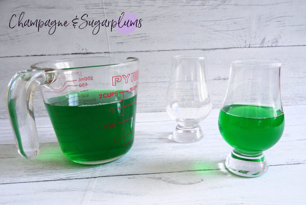 Pouring lime jelly into a dessert glass by Champagne and Sugarplums