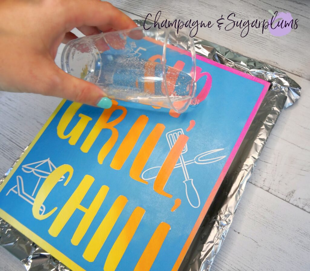 Pouring resin from a plastic cup over a wood sign on a tray covered with tin foil by Champagne and Sugarplums