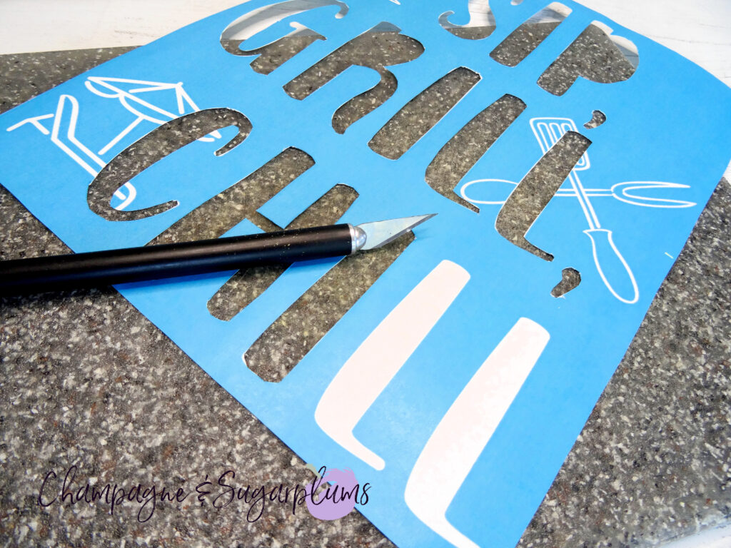 Cutting white letters out of a blue template on a cutting board by Champagne and Sugarplums