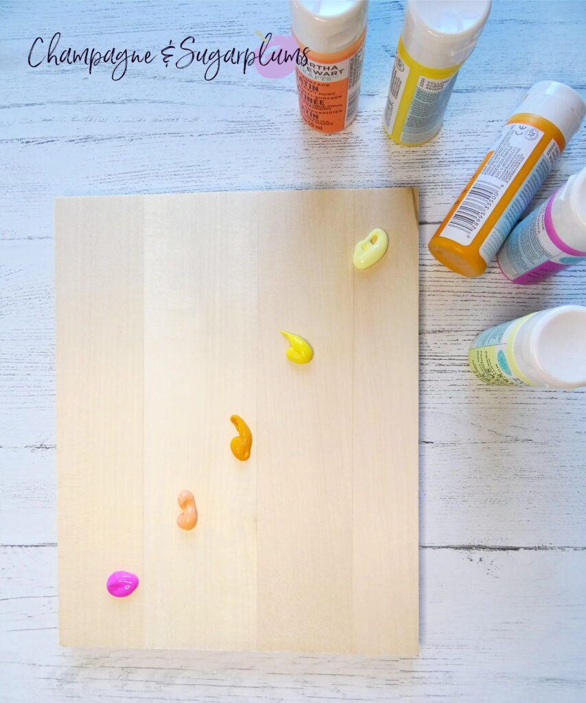 Adding paint in blobs to a wood board in pinks, oranges and yellows by Champagne and Sugarplums