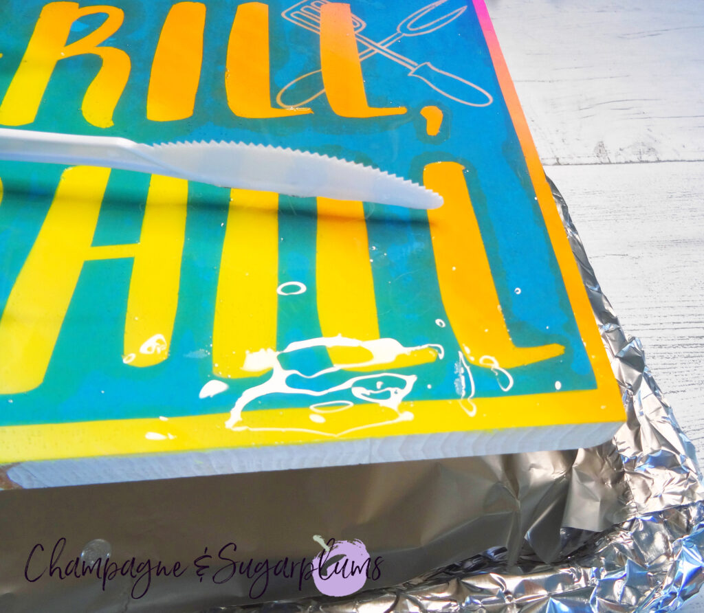Spreading resin over a wood sign on a tray covered with tin foil by Champagne and Sugarplums
