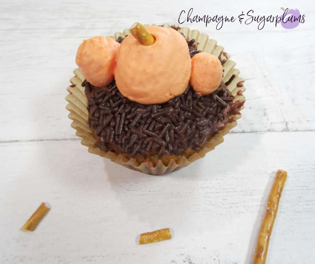 Adding pretzel stems to icing pumpkins on a chocolate cupcake on a white background by Champagne and Sugarplums
