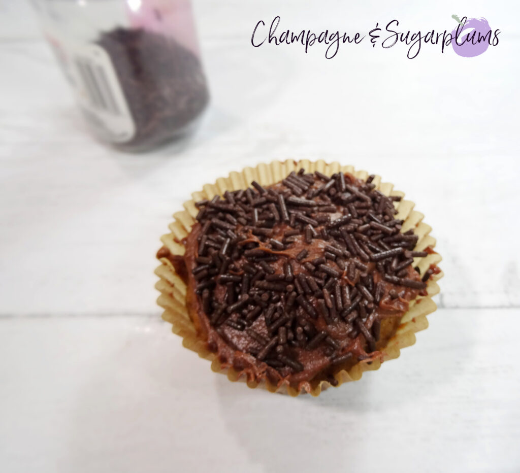 Iced cupcake with chocolate icing and sprinkles on a white background by Champagne and Sugarplums