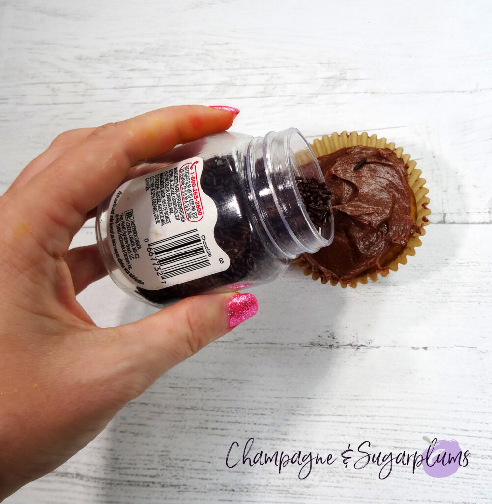 Adding chocolate sprinkles on top of an iced cupcake on a white background by Champagne and Sugarplums