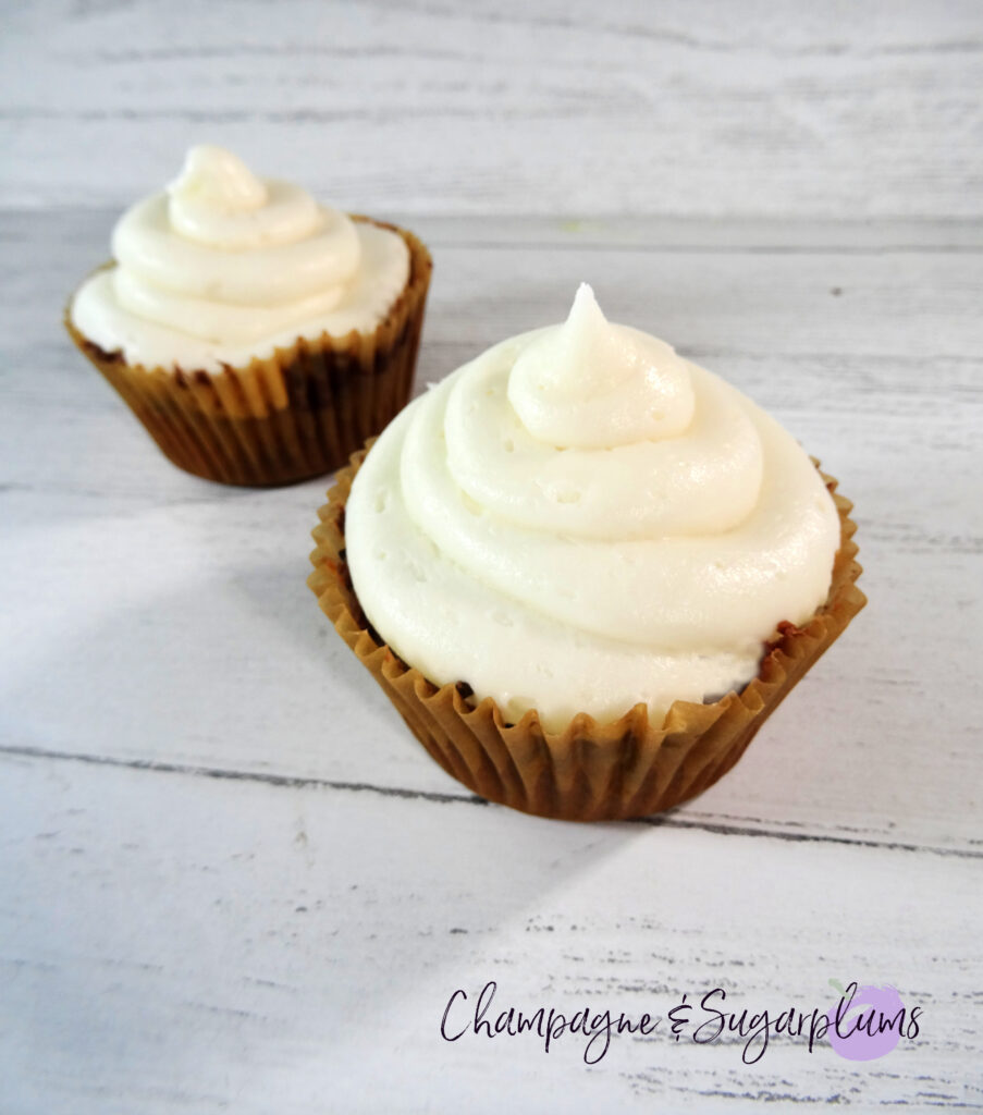 Pumpkin Cupcakes with white icing on a white background by Champagne and Sugarplums