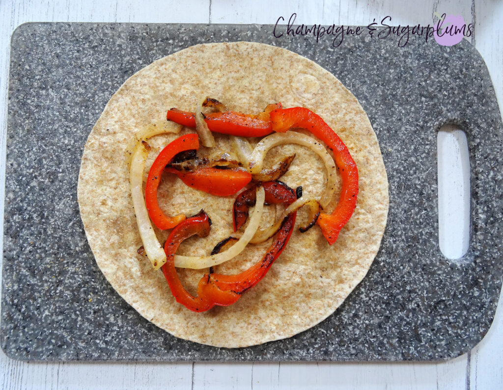 Adding onions and peppers to a quesadilla on a grey cutting board by Champagne and Sugarplums