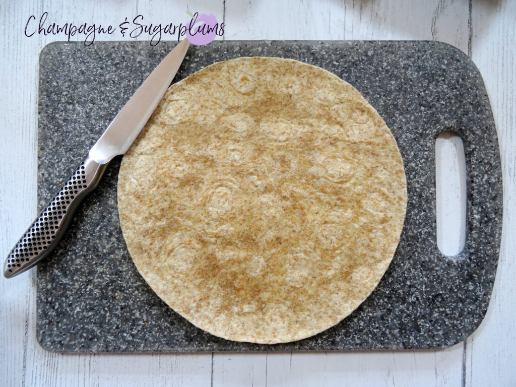 A tortilla on a grey cutting board by Champagne and Sugarplums