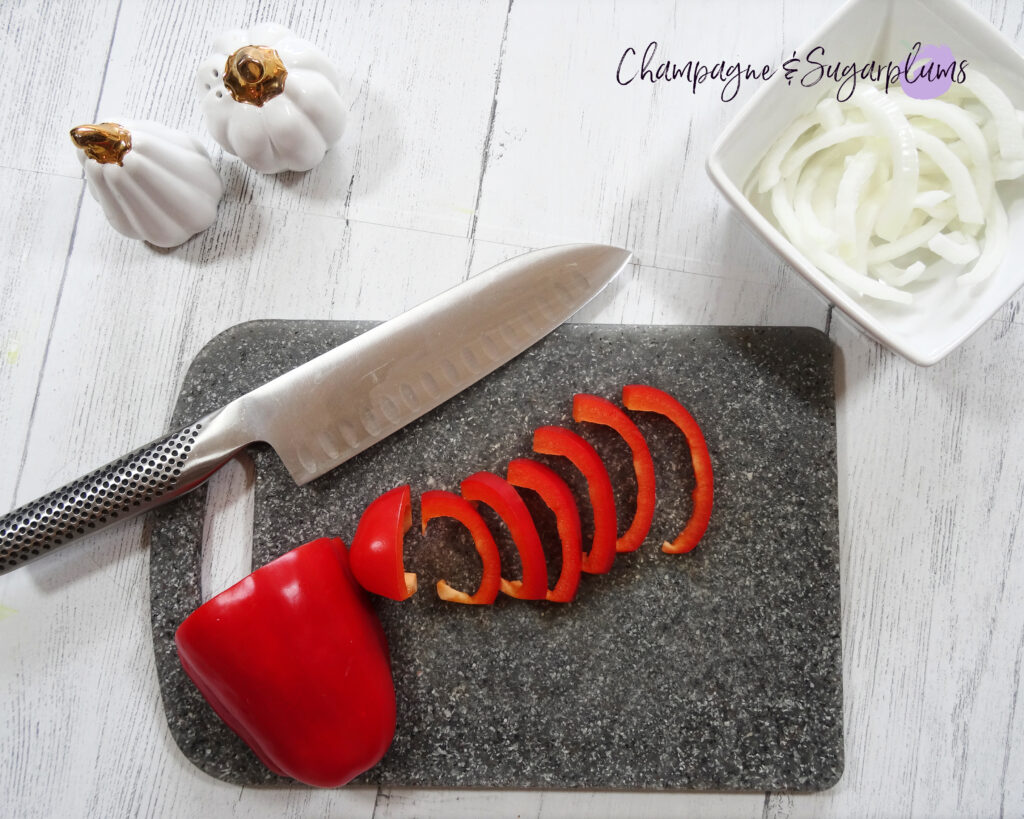 Cutting up a red pepper on a grey cutting board by Champagne and Sugarplums