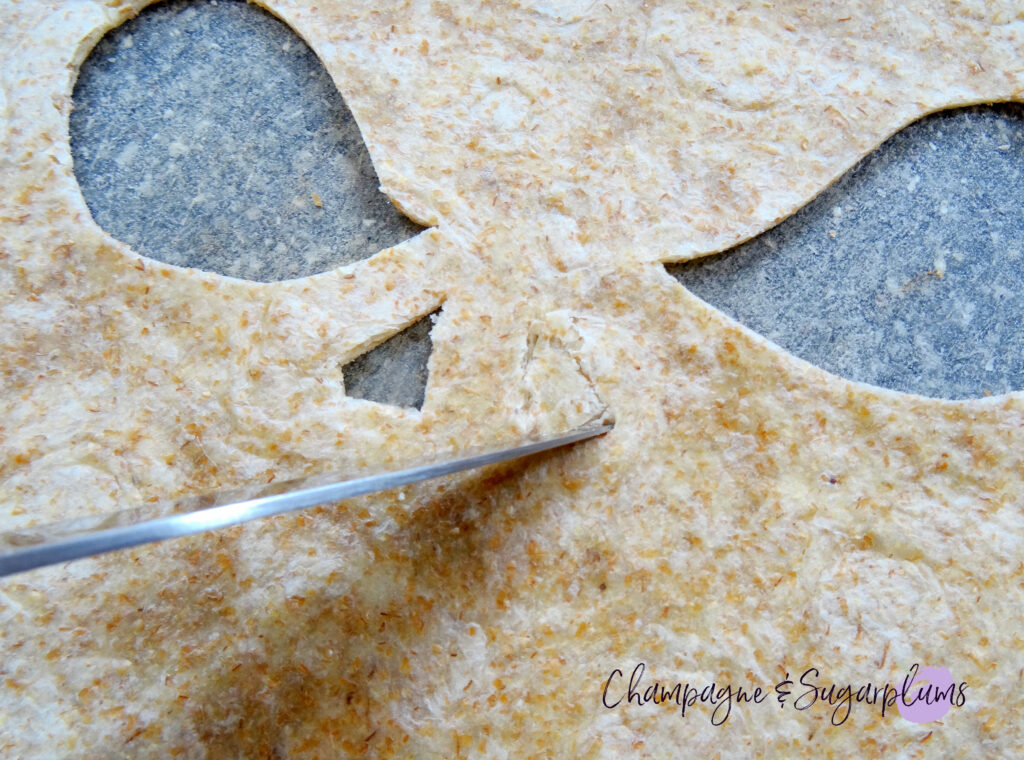 Cutting a nose into a tortilla on a grey cutting board by Champagne and Sugarplums