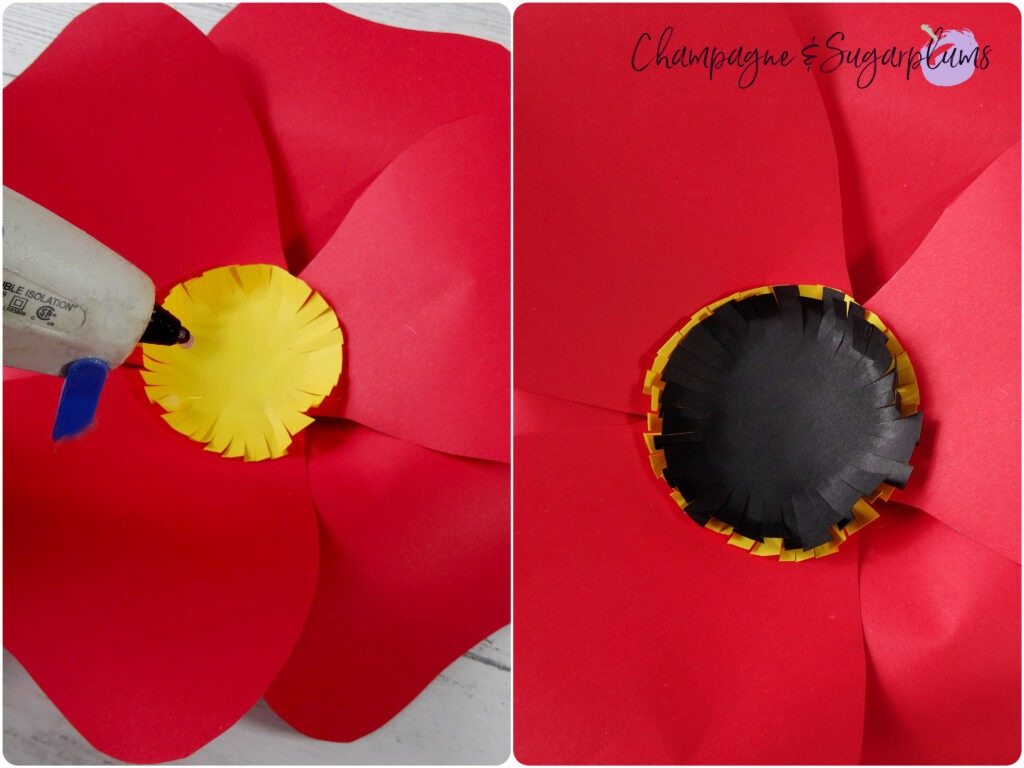 Gluing first a yellow and then a black paper circle to the centre of red paper flower by Champagne and Sugarplums