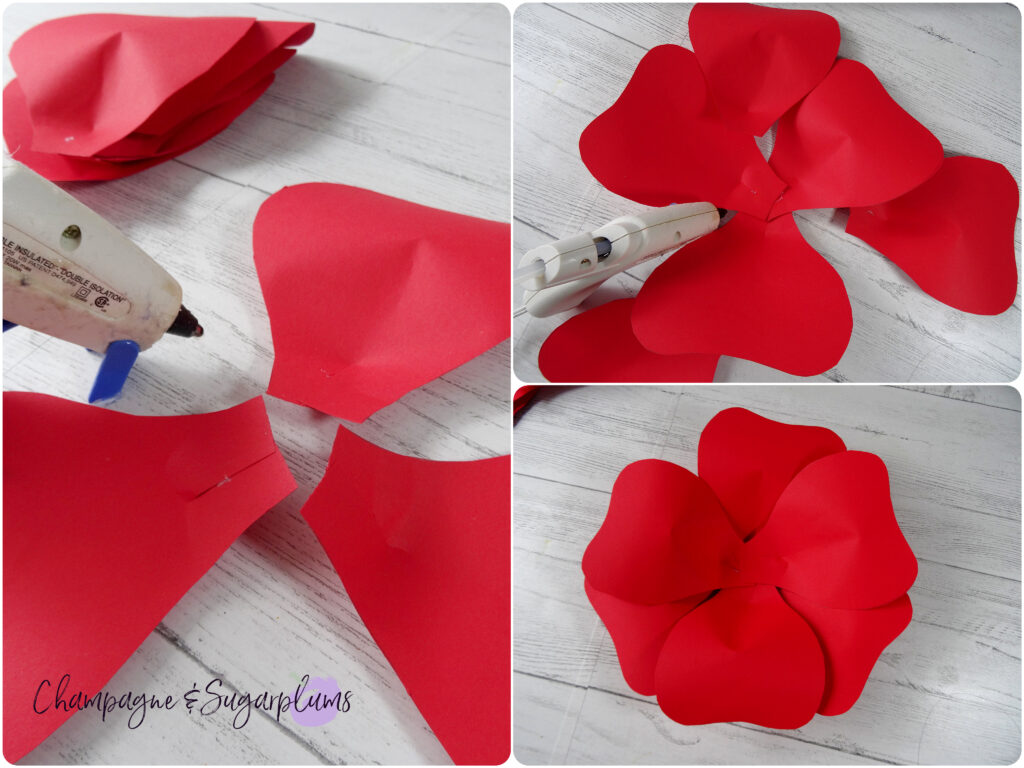 Gluing red paper flower petals together with a hot glue to create a large flower by Champagne and Sugarplums
